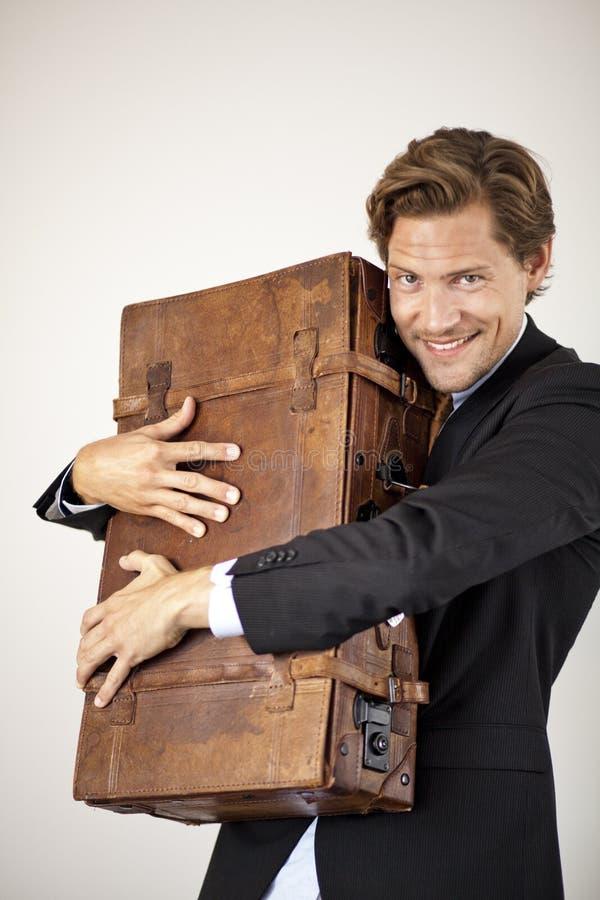 Młody biznesmen obejmuje jego starą walizkę fotografia royalty free