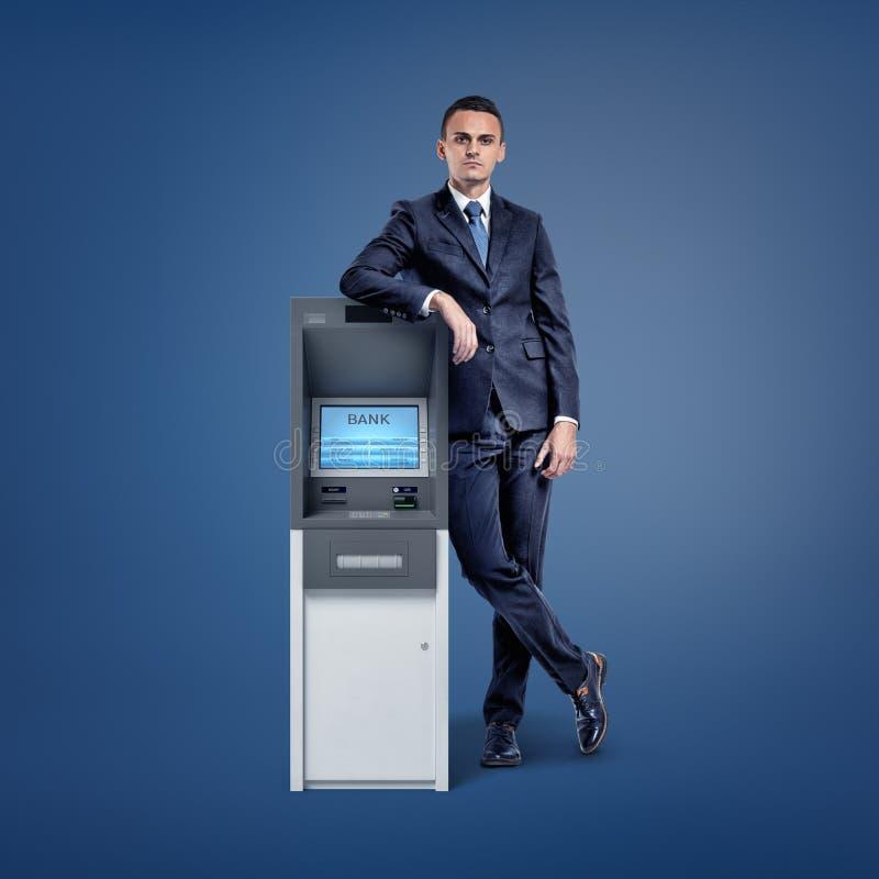 Młody biznesmen opiera na małej banka ATM maszynie na zmroku - błękitny tło obrazy royalty free