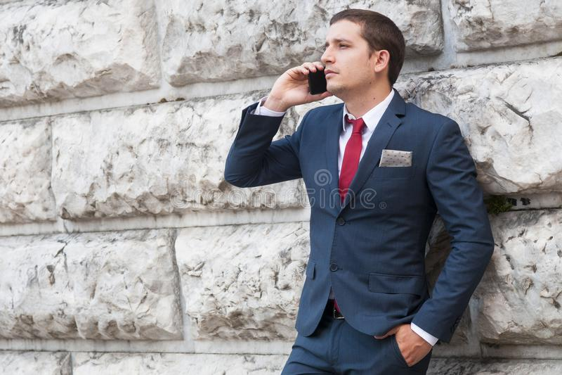 Młody biznesmen opowiada przy smartphone ag w krawacie i kostiumu obraz stock