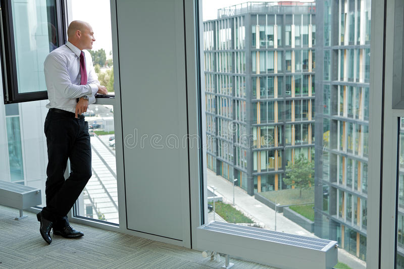 Młody biznesmen patrzeje przez okno obrazy royalty free