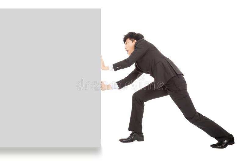 Młody biznesmen pcha pustą deskę na bielu obrazy stock