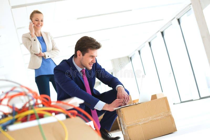 Młody biznesmen pracuje na laptopie podczas gdy żeński kolega używa telefon komórkowego w nowym biurze obraz royalty free