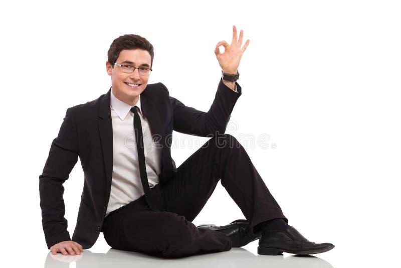 Młody biznesmen relaksuje OK znaka i pokazuje. obraz royalty free