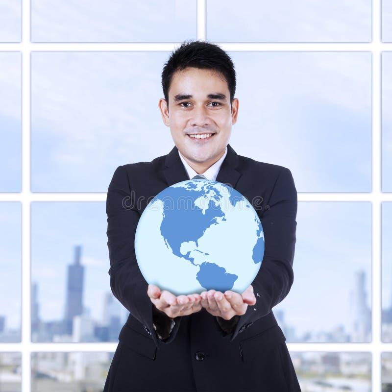 Młody biznesmen trzyma kulę ziemską zdjęcie royalty free