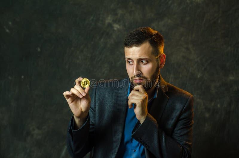 Młody biznesmen trzyma monetę bitcoite w jego ręce fotografia royalty free