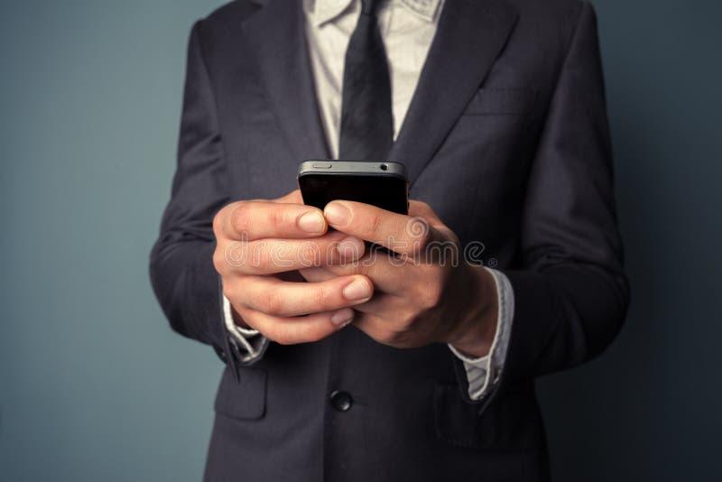 Młody biznesmen używa mądrze telefon fotografia royalty free