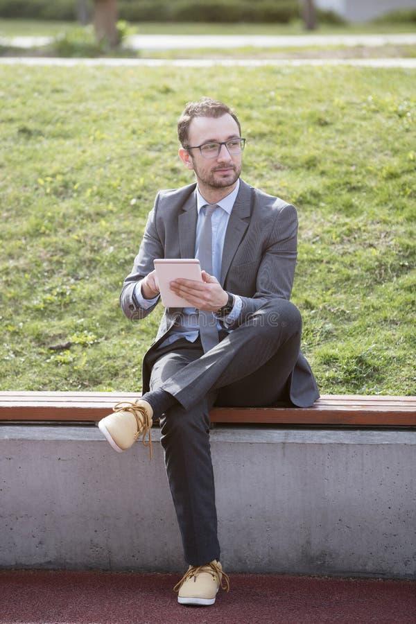 Młody biznesmen używa pastylka przyrząd na ławce w parku obraz stock