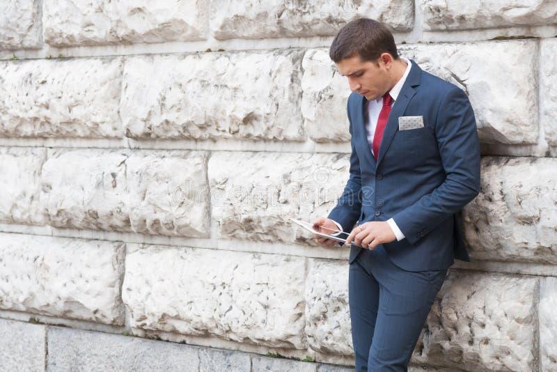Młody biznesmen w kostiumu i krawata czytaniu od pastylki przeciw zdjęcie stock