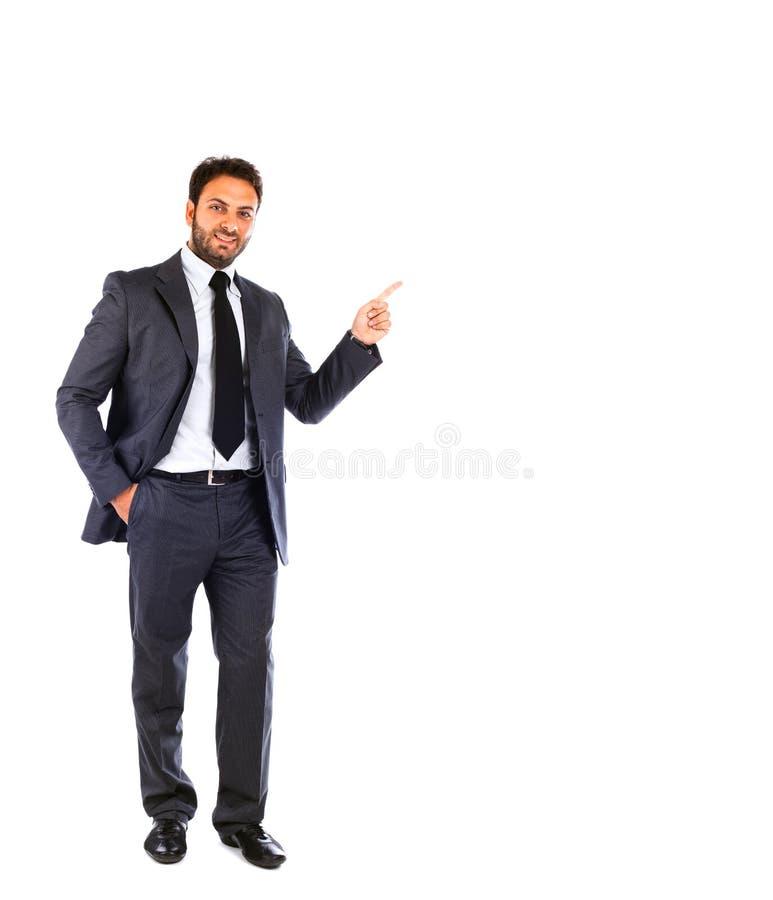 Młody biznesmen wskazuje na pustym tle zdjęcia royalty free