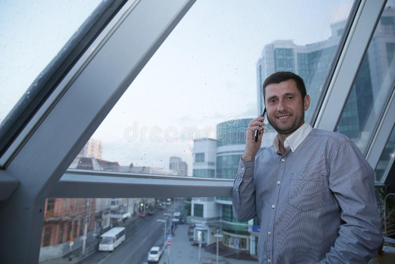 Młody biznesmen z uśmiechem na jego twarzy opowiada na jego telefonie komórkowym przeciw tłu panoramiczny okno na wysokim f zdjęcia stock