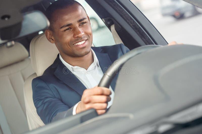 Młody biznesmena kierowcy obsiadanie wśrodku samochodowej mienie kierownicy jedzie szczęśliwego frontowego outside widok w górę fotografia royalty free