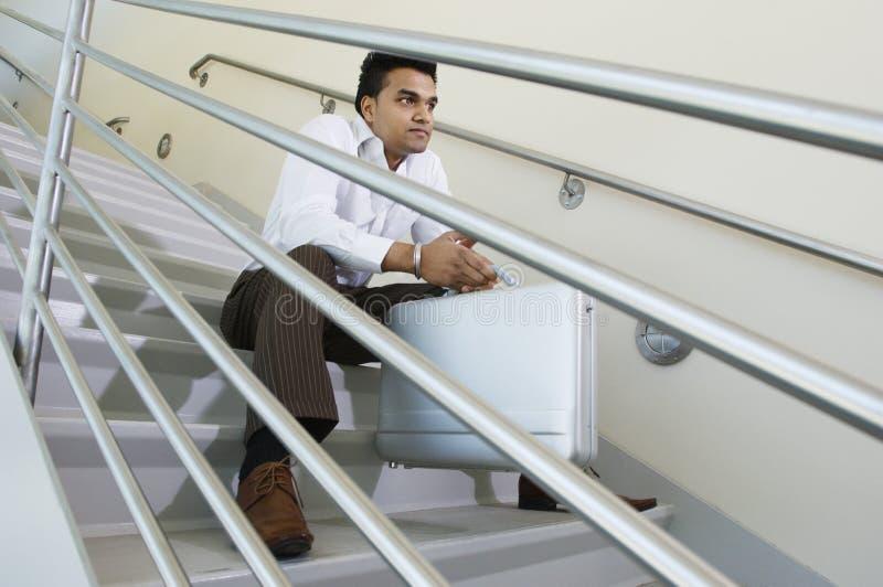 Młody biznesmena obsiadanie Na schody fotografia royalty free