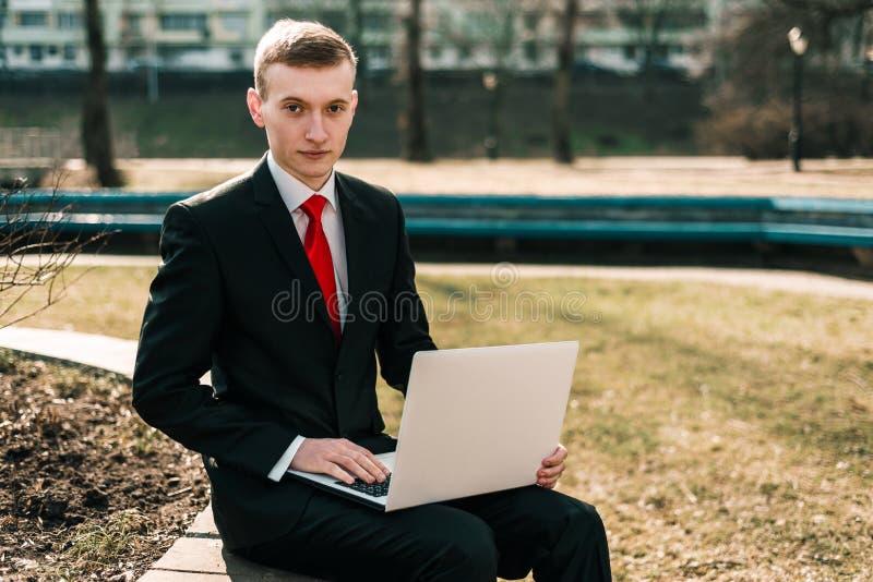 M?ody biznesmena obsiadanie z laptopem na parkowej ?awce facet w kostiumu z czerwonym krawatem _ Daleki pracy poj?cie obrazy royalty free