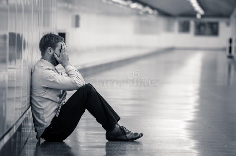 Młody biznesmena płacz porzucał przegranego w depresji obsiadaniu na zmielonym metrze fotografia stock