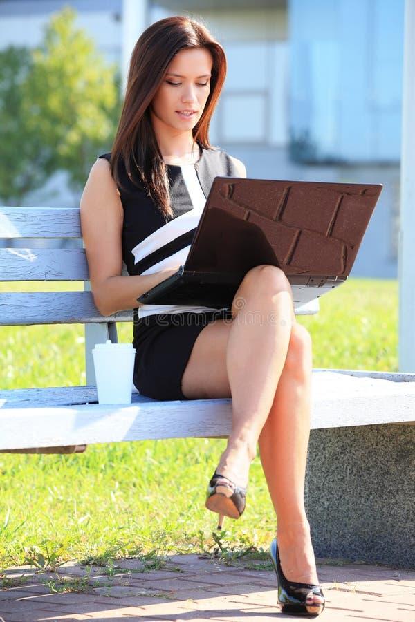 Młody biznesowej kobiety obsiadanie na parkowej ławce zdjęcia royalty free