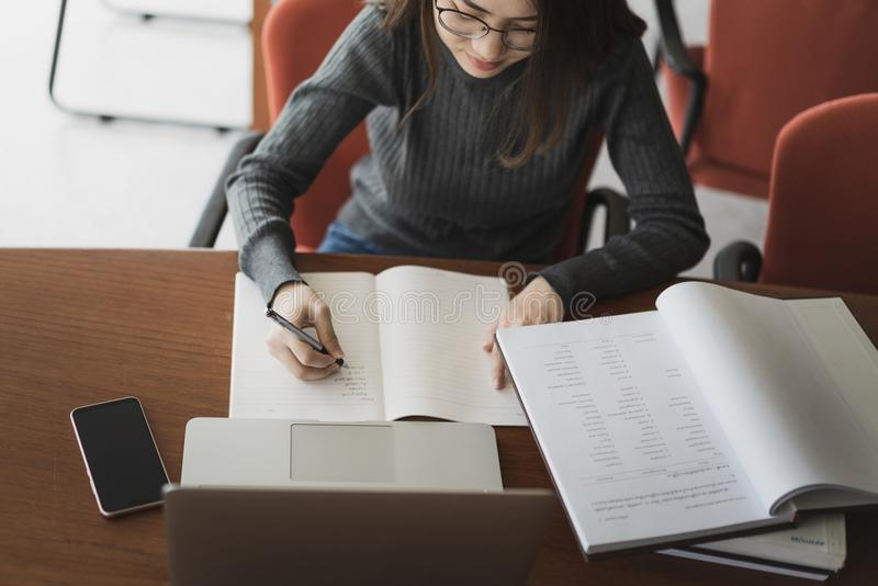 Młody biznesowej kobiety obsiadanie przy stołowymi i biorą notatkami w notatniku, Na stole jest laptopem, Smartphone i filiżanka  obrazy stock