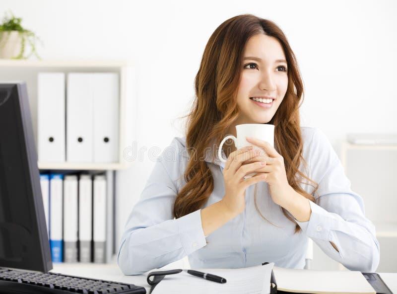 Młody biznesowej kobiety pić kawowy i przyglądający zdjęcia stock