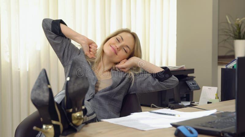 Młody biznesowej kobiety ziewanie przy nowożytnym biurowym biurkiem przed laptopem zdjęcie stock