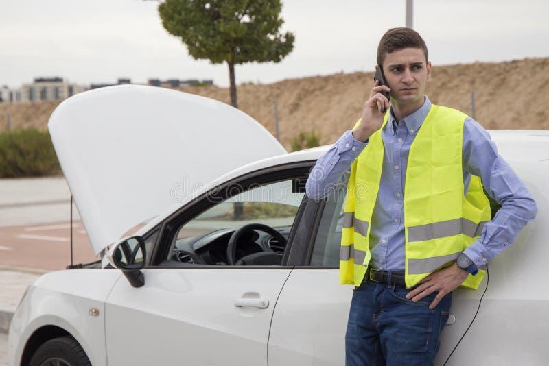 Młody biznesowy mężczyzna jest ubranym odbijającą kamizelkę na zewnątrz samochodu, czeka pomoc fotografia stock
