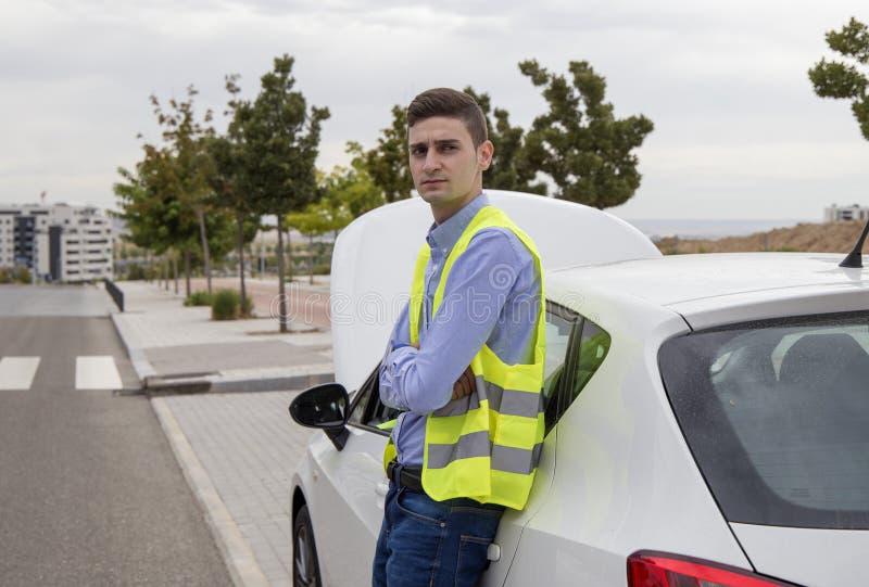 Młody biznesowy mężczyzna jest ubranym odbijającą kamizelkę, outside samochód obrazy stock