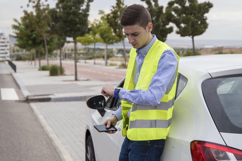 Młody biznesowy mężczyzna jest ubranym odbijającą kamizelkę, outside samochód fotografia royalty free