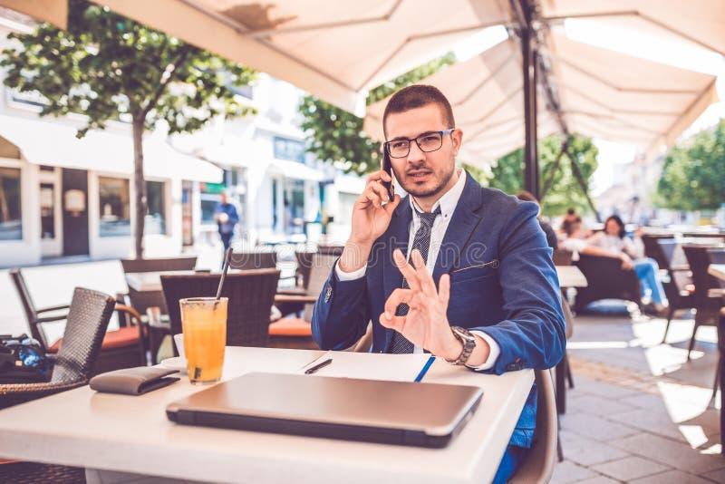 Młody biznesowy mężczyzna opowiada telefonu komórkowego seansu ok gestem podczas kawowej przerwy w kawiarni zdjęcie royalty free