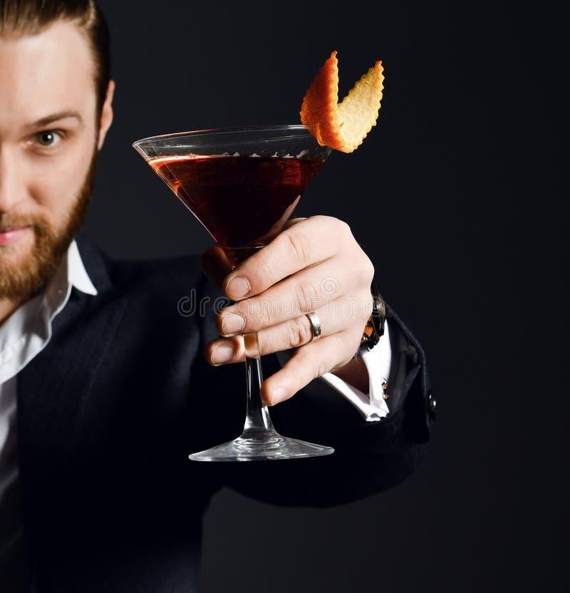Młody biznesowy mężczyzna pije czerwonego koktajl w białej koszula i kurtka pijemy z pomarańcze w Martini szkle zdjęcie stock