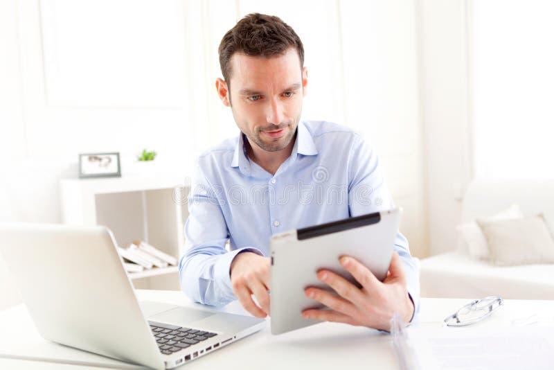Młody biznesowy mężczyzna pracuje w domu na jego pastylce obraz stock