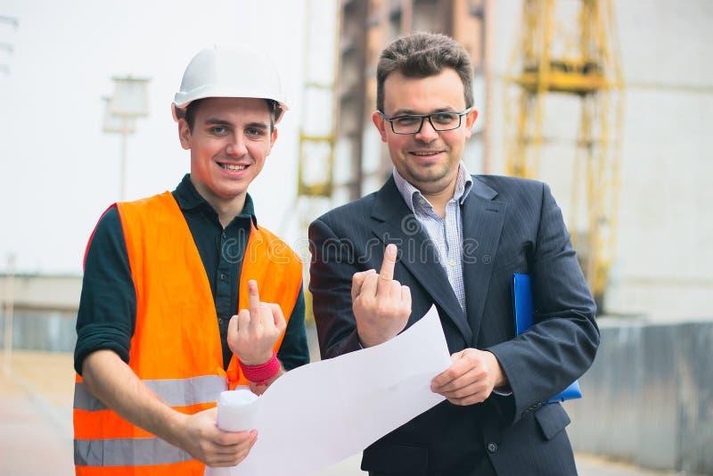 Młody biznesowy mężczyzna przy budowa planami biznesowymi robić ich pracie skuteczna Oba przedstawień środkowy palec fotografia royalty free
