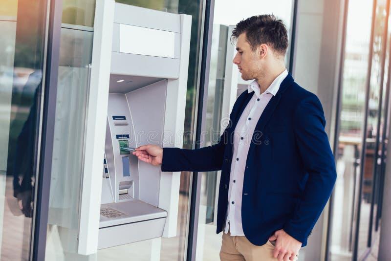 Młody biznesowy mężczyzna używa ATM zdjęcia royalty free