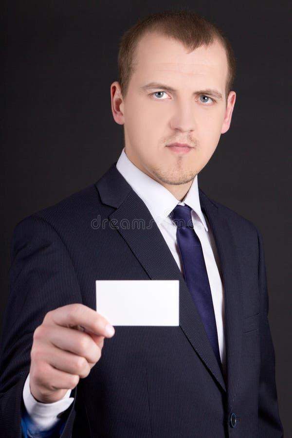 Młody biznesowy mężczyzna w kostiumu pokazuje odwiedzający kartę nad popielatym zdjęcie stock