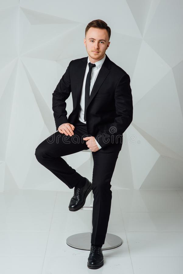 Młody biznesowy mężczyzna w nowożytnym kostiumu obsiadaniu na krześle obraz stock