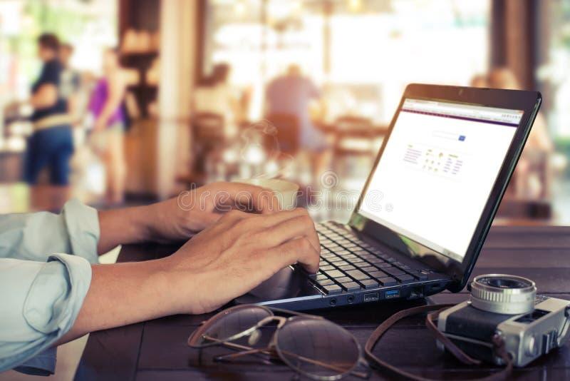 młody biznesowy mężczyzna wręcza ruchliwie działanie na jego laptopu obsiadaniu przy drewnianym stołem obrazy royalty free