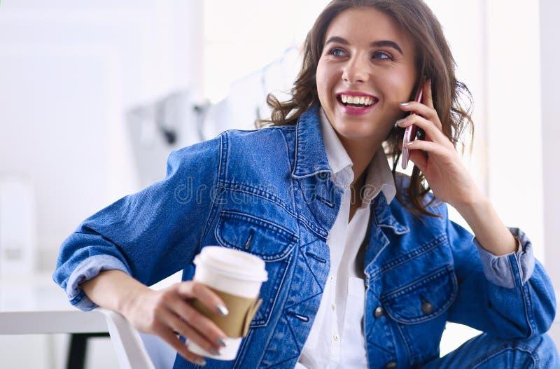 M?ody bizneswoman opowiada na telefonie w sklepie z kaw? fotografia royalty free