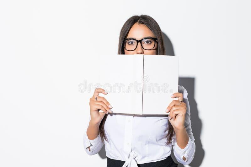 Młody bizneswoman patrzeje nad książkową pokrywą na białym tle zdjęcia royalty free