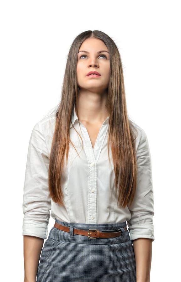 Młody bizneswoman patrzeje upwards zamyślenie odizolowywającego na białym tle zdjęcia stock