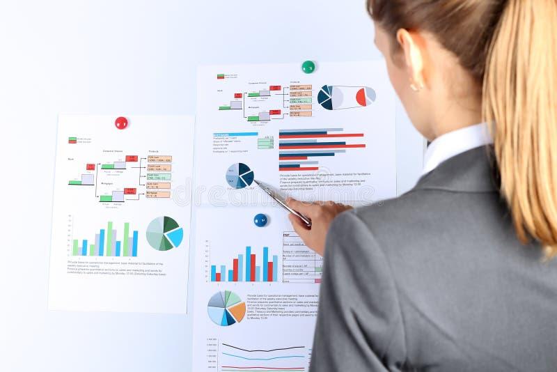 Młody bizneswoman pokazuje wykresy piórem Presentatoin obrazy stock