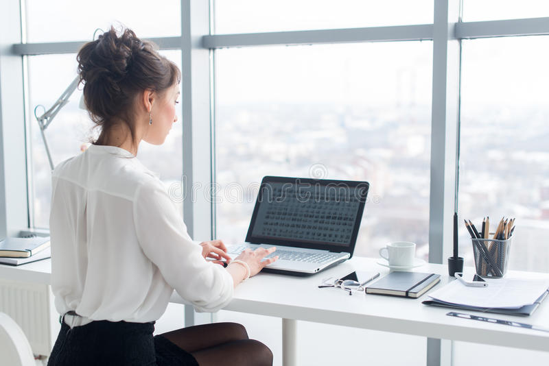 Młody bizneswoman pracuje w biurze, pisać na maszynie, używać komputer Skoncentrowanego kobiety gmerania ewidencyjny online, tyły zdjęcie stock