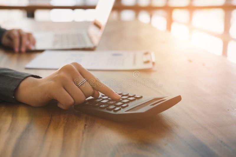 Młody bizneswoman pracuje z kalkulatorem, biznesowy dokument a fotografia stock