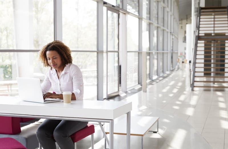 Młody bizneswoman przy biurkiem pracuje na jej laptopie obrazy stock