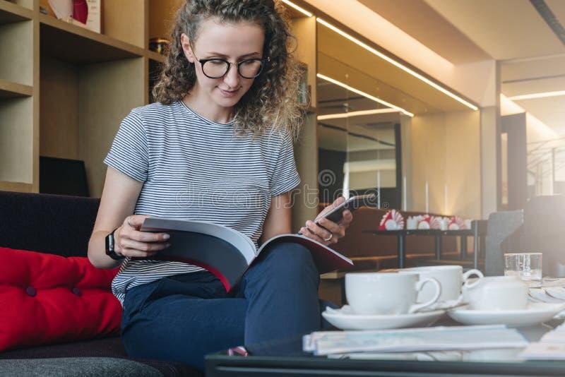 Młody bizneswoman siedzi na kanapie w hotelu lobby i czyta książkę, restauracja, kawiarnia, magazyn, katalog zdjęcia royalty free