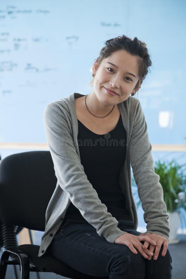 Młody bizneswoman siedzi w biurze w przypadkowych ubraniach, portret zdjęcie stock