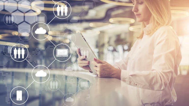 Młody bizneswoman stoi pastylka komputer i używa W przedpolu są wirtualne ikony z chmurami, cyfrowi gadżety zdjęcie royalty free