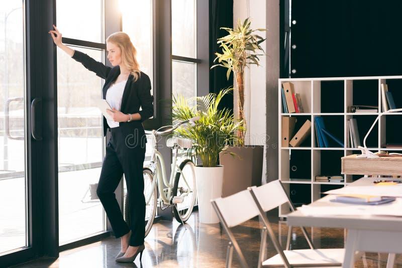 Młody bizneswoman trzyma cyfrową pastylkę i patrzeje okno w nowożytnym biurze obrazy stock