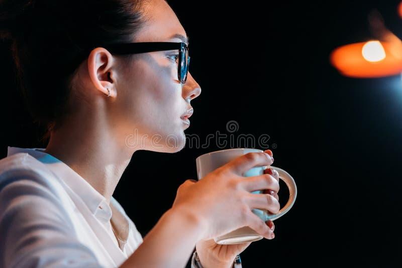 Młody bizneswoman trzyma filiżankę w eyeglasses podczas gdy pracujący póżno w biurze fotografia stock