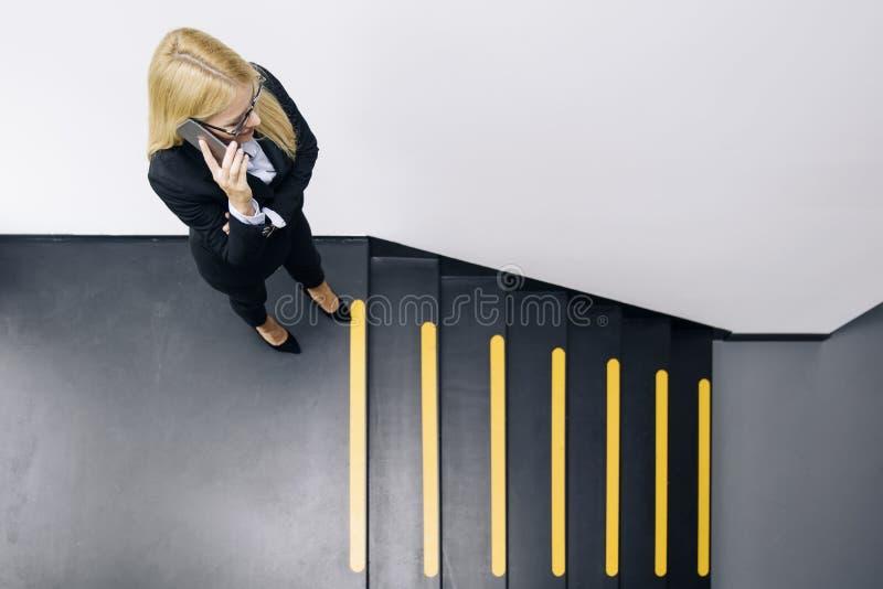 Młody bizneswoman używa telefon komórkowego podczas gdy wspinaczki schodki obrazy stock