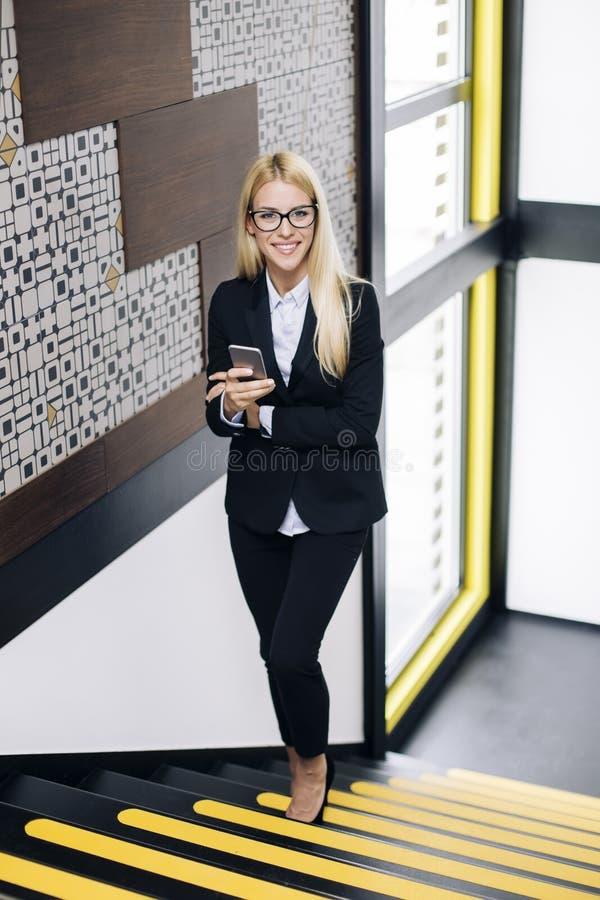 Młody bizneswoman używa telefon komórkowego w biurze zdjęcie stock