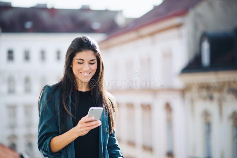Młody bizneswoman z smartphone pozycją na tarasowym na zewnątrz biura w mieście fotografia stock