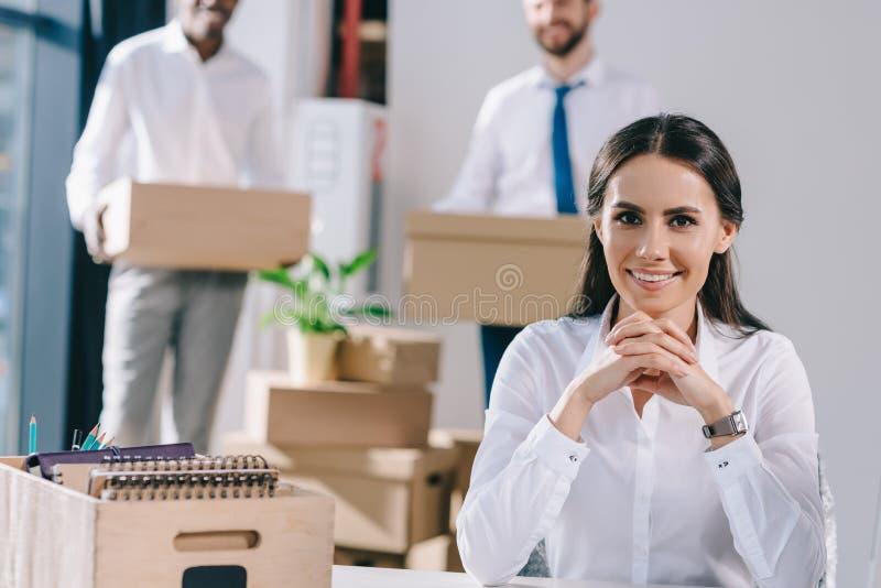 młody bizneswomanu obsiadanie i ono uśmiecha się przy kamerą podczas gdy męscy koledzy trzyma pudełka za zdjęcie royalty free