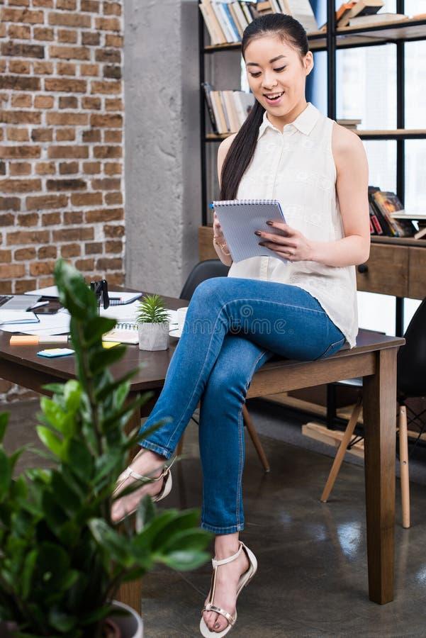 Młody bizneswomanu obsiadanie na stołu i mienia notatniku zdjęcie royalty free